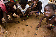 Children play owari, a traditional african game, with seeds in the dirt in the village of Wantugu, northern Ghana on Friday March 27, 2009..