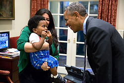 President Barack Obama greets a little boy held by Ferial Govashiri, Personal Aide to the President, in the Outer Oval Office, Oct. 24, 2014. (Official White House Photo by Pete Souza)<br /> <br /> This official White House photograph is being made available only for publication by news organizations and/or for personal use printing by the subject(s) of the photograph. The photograph may not be manipulated in any way and may not be used in commercial or political materials, advertisements, emails, products, promotions that in any way suggests approval or endorsement of the President, the First Family, or the White House.