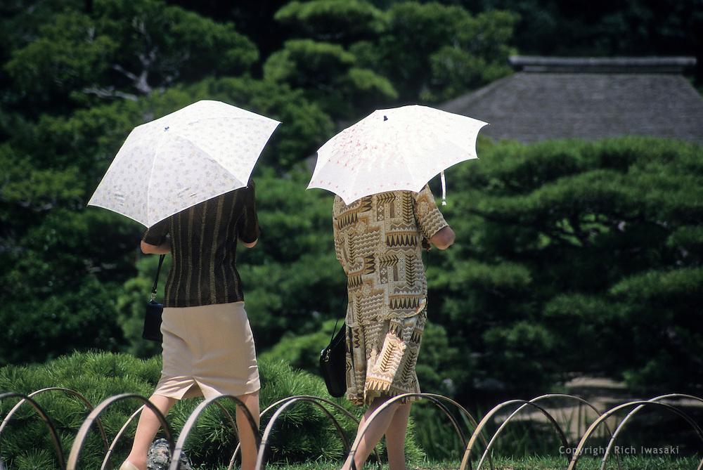 Two women use umbrellas for sun protection during a visit to Korakuen garden in Okayama city, Okayama Prefecture, Japan