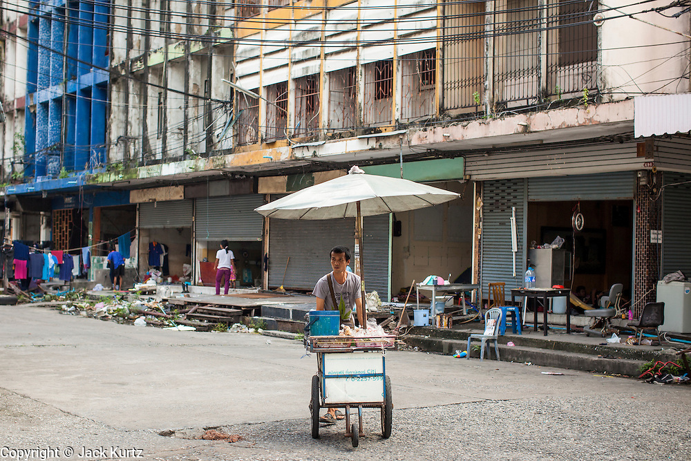 "03 DECEMBER 2012 - BANGKOK, THAILAND:  A food vendor pushes his cart through the ""Washington Square"" district in Bangkok. Workers live in the buildings they are demolishing until the buildings are completely uninhabitable. Washington Square was a notorious adult ""entertainment"" and red light district on Sukhumvit Soi 22 in Bangkok. Many of the bars and massage parlors catered in the district to older American and European men and opened in the 1960's when Bangkok was a ""R&R"" destination for American servicemen in Vietnam. It's being torn down to make way for new high rise hotels and condominiums.        PHOTO BY JACK KURTZ"