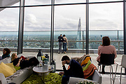Visitors admire London skyline seen from the Sky Garden on the top of the Walkie Talkie building in the City of London. Couples and singles are seen small with the expanse of wide architecture with the Shard in the distance. 20 Fenchurch Street is a commercial skyscraper in London that takes its name from its address on Fenchurch Street, in the historic City of London financial district. It has been nicknamed The Walkie-Talkie because of its distinctive shape. Construction was completed in spring 2014, and the top-floor 'sky garden' was opened in January 2015. The 34-storey building is 160 m (525 ft) tall, making it the fifth-tallest building in the City of London. Designed by architect Rafael Viñoly and costing over £200 million.