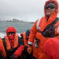 Tourists brave wind, rain and waves in a Zodiac raft as a guide drives them back to their ship from Half Moon Island, Antarctica.