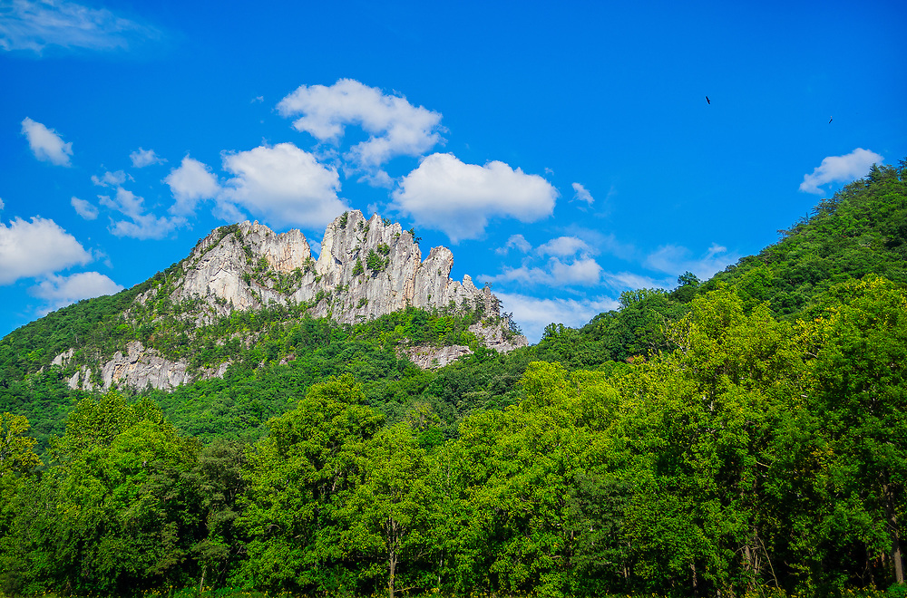 Full view of Seneca Rocks, West Virginia in the day, clouds with blue sky and birds circling over head.