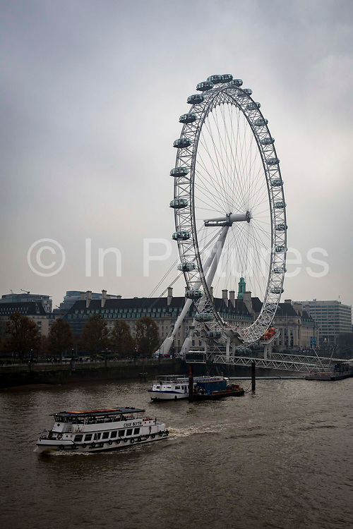 A view of the London Eye overlooking the River Thames on Lambeth, London, United Kingdom. The buildings behind hold the London Dungeon, The London Aquarium, and St Thomas Hospital.