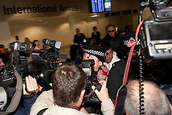 © licensed to London News Pictures. Manchester, UK  14/02/2012. Carlos Tevez arrives at Manchester Airport to rejoin the Manchester City squad. He is surrounded by a large media scrum. Photo credit should read Joel Goodman/LNP