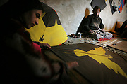 Noor Agha, about 52, at right, and Farida, the second wife, left, make kites in the house, Kabul, Afghanistan, Thursday, March, 8, 2007. Noor Agha is a renowned kite maker who made kites for the movie makers of the best-selling novel, The Kite Runner, which will be distributed by Dreamworks and Paramount Vantage in Nov. this year. Noor Agha's wives, using their special glue, help him produce enough kites to please the clients' needs. Some of his children can also make their own kites with plastic bags and bamboo sticks. As the Afghan New Year's Day (Nawruz) approaching on March 21, the finger tips of Noor Agha's family got busier for mass production.