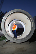 Construction Man Wearing A Safety Vest And Hard Hat Standing In A Cement Pipe