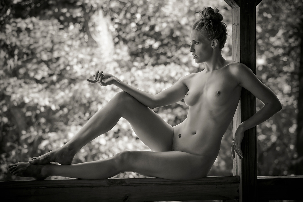 Black and white photo of a nude woman with her hair in a bun sitting on a porch railing with a forest in the background