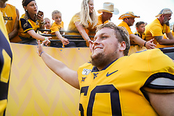 Sep 14, 2019; Morgantown, WV, USA; West Virginia Mountaineers offensive lineman Noah Drummond (60) celebrates with fans after beating the North Carolina State Wolfpack at Mountaineer Field at Milan Puskar Stadium. Mandatory Credit: Ben Queen-USA TODAY Sports
