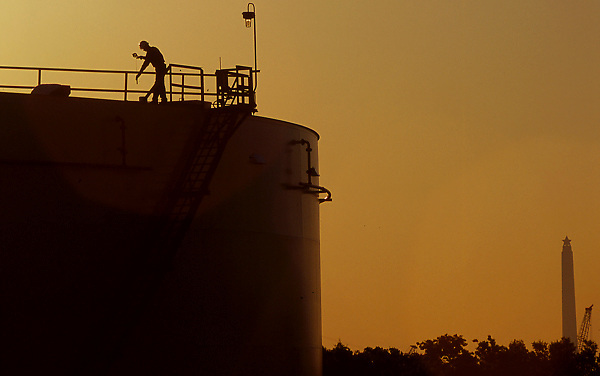 Silhouette of one man working on top of a tank at a petrochemical plant in Houston, Texas at dusk with San Jacinto Monument on the horizon.