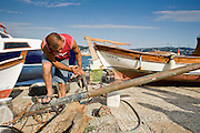 08 AUGUST 2007 -- ISTANBUL, TURKEY: A man makes repairs on his small boat along the Bosphorus Straits in Istanbul, Turkey. Istanbul, a city of about 14 million people, and the largest city in Turkey, straddles the Bosphorus Straits between Europe and Asia. It is one of the oldest cities in the world. It was once the center of the Eastern Roman Empire and was called Constantinople, named after the Roman Emperor Constantine. In 1453, Mehmet the Conqueror, Sultan of the Ottoman Empire, captured the city and made it the center of the Ottoman Turkish Empire until World War I. After the war, the Ottoman Empire was dissolved and modern Turkey created. The capitol was moved to Ankara but Istanbul (formerly Constantinople) has remained the largest, most diverse city in Turkey.    Photo by Jack Kurtz