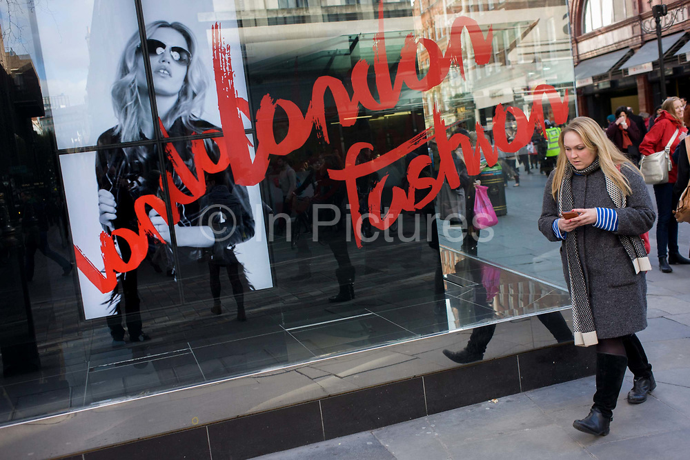 A woman walks past a window ad for the forthcoming London Fashion Week. A model is seen on a TV screen as it scrolls through a loop of film, telling us how stylish and modern the annual event will soon be in the capital. The words London and Fashion have been written across the window of a sunglasses retailer on Long Acre in the capital's Covent Garden. Both model and passer-by are holding possessions in the same way and others are in the background on this busy junction in the West End.