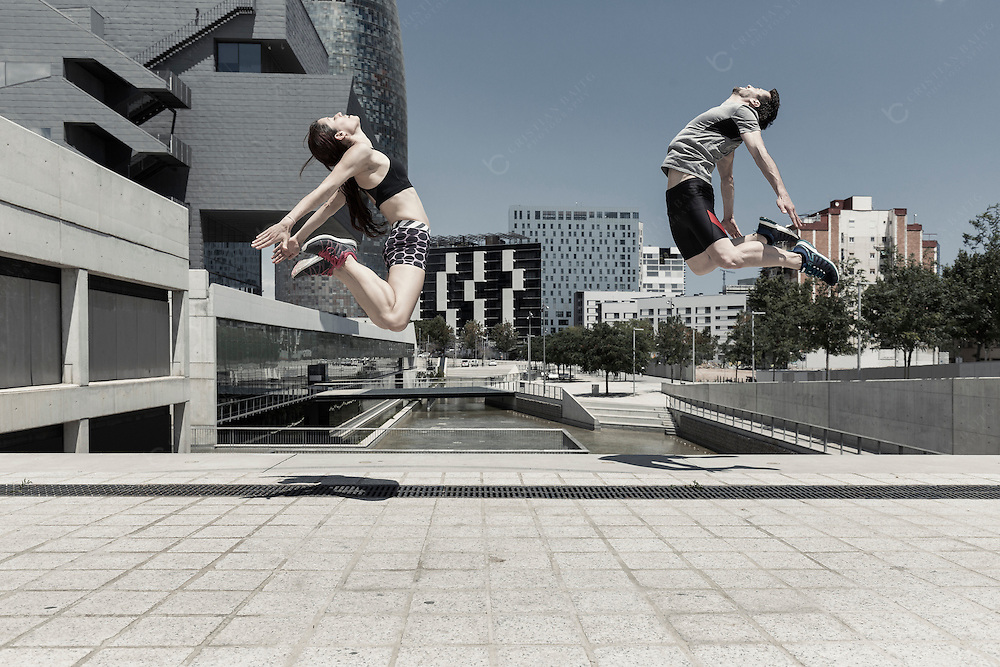 Man and woman jumping in front of city skyline