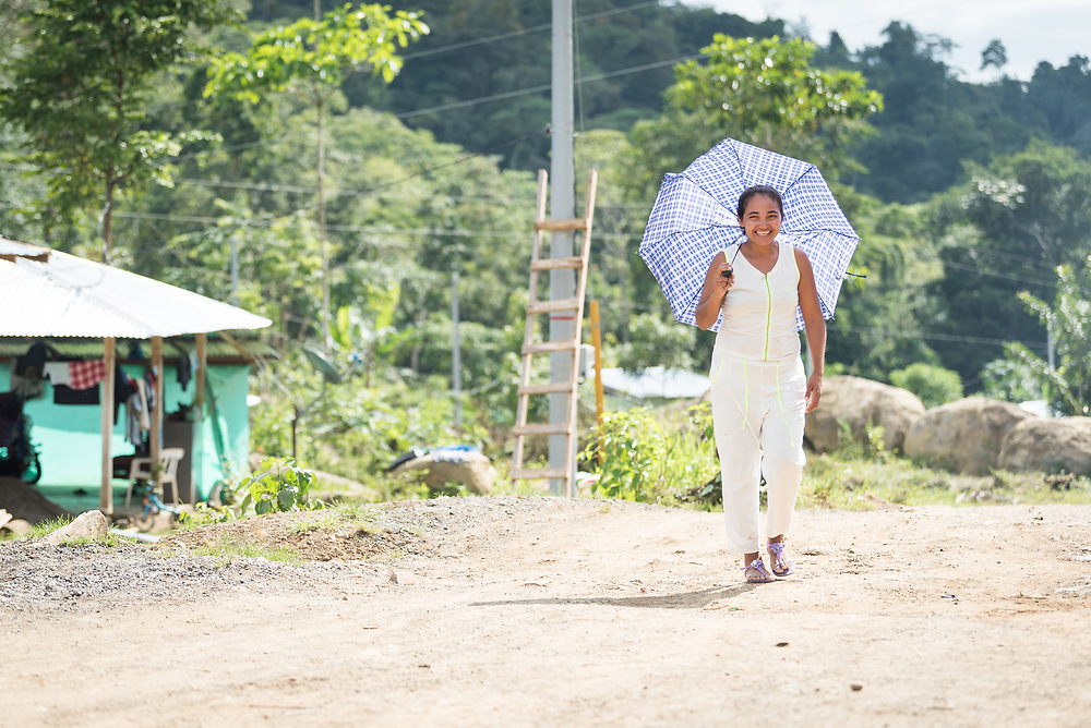 16 November 2018, San José de León, Mutatá, Antioquia, Colombia: A woman walks through the village with an umbrella as protection from the sun. Following the 2016 peace treaty between FARC and the Colombian government, a group of ex-combatant families have purchased and now cultivate 36 hectares of land in the territory of San José de León, municipality of Mutatá in Antioquia, Colombia. A group of 27 families first purchased the lot of land in San José de León, moving in from nearby Córdoba to settle alongside the 50-or-so families of farmers already living in the area. Today, 50 ex-combatant families live in the emerging community, which hosts a small restaurant, various committees for community organization and development, and which cultivates the land through agriculture, poultry and fish farming. Though the community has come a long way, many challenges remain on the way towards peace and reconciliation. The two-year-old community, which does not yet have a name of its own, is located in the territory of San José de León in Urabá, northwest Colombia, a strategically important corridor for trade into Central America, with resulting drug trafficking and arms trade still keeping armed groups active in the area. Many ex-combatants face trauma and insecurity, and a lack of fulfilment by the Colombian government in transition of land ownership to FARC members makes the situation delicate. Through the project De la Guerra a la Paz ('From War to Peace'), the Evangelical Lutheran Church of Colombia accompanies three communities in the Antioquia region, offering support both to ex-combatants and to the communities they now live alongside, as they reintegrate into society. Supporting a total of more than 300 families, the project seeks to alleviate the risk of re-victimization, or relapse into violent conflict.