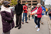 29 OCTOBER 2020 - DES MOINES, IOWA: RUTH THOMSON, right, hands out popcorn to voters waiting in line at the Polk County Auditor's Office in Des Moines. There have been long lines for early voting all month. According to the Polk County Auditor's Office, as of October 27, 120,752 ballots have been returned of the 144,028 ballots requested for a return rate of 83.84 percent. Iowa starts counting early ballots the morning of Nov. 3.     PHOTO BY JACK KURTZ
