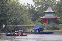 © Licensed to London News Pictures. 04/06/2021. London, UK. Members of a film crew get caught in the rain on West Boating Lake in Victoria Park, east London. Photo credit: Marcin Nowak/LNP