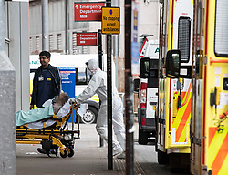 **Face has been pixelated to hide the identity of patient**<br /> © Licensed to London News Pictures. 02/04/2020. London, UK. An ambulance worker wearing personal protective clothing and a medical face mask transports a patient in to The Royal London Hospital in East London, during a pandemic outbreak of the Coronavirus COVID-19 disease. Members of the public have been told they can only leave their homes when absolutely essential, in an attempt to fight the spread of COVID-19. Photo credit: Ben Cawthra/LNP