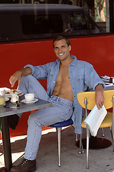 man with an open shirt at a cafe