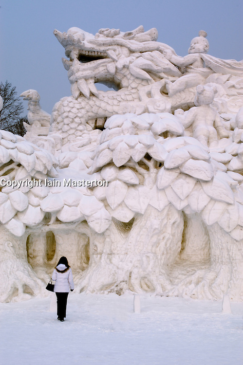 Woman looking at large snow sculpture of a dragon at Harbin Snow Festival in China