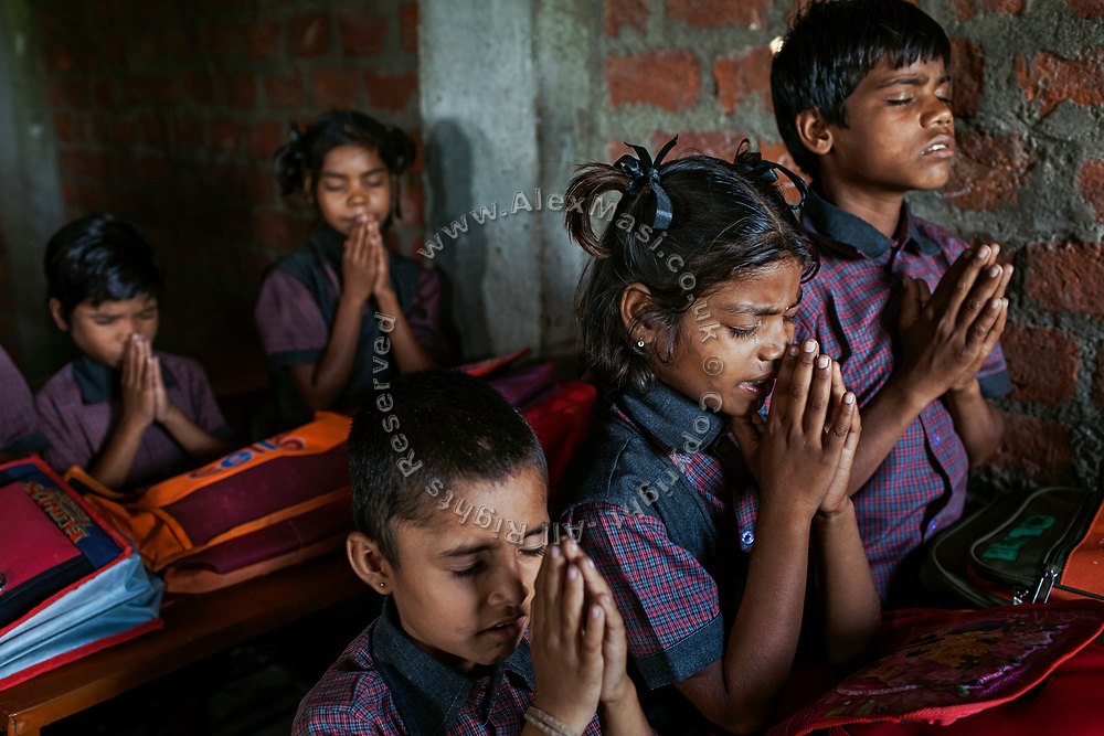 Among other pupils, Poonam, 9, (centre/front) her brother Ravi, 11, (right/front) their sister Jyoti, 10, (right/back) are praying on their very first day in a cozy, private school located by their newly built home in Oriya Basti, one of the water-contaminated colonies in Bhopal, central India, near the abandoned Union Carbide (now DOW Chemical) industrial complex, site of the infamous '1984 Gas Disaster'.