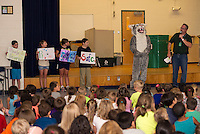 "Hunter Currier ""Ready to Learn"" , Zaria Ainsworth ""Responsible"", Phoebe Reynolds ""Respectful"" and Tyler Fleury ""Safe"" help to bring PBIS (Positive Behavioral Intervention Suppports) with Whiskers the mascot and Principal Johnson on Thursday afternoon at Woodland Heights Elementary School.  (Karen Bobotas/for the Laconia Daily Sun)"