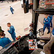 Engineering ground staff of the Red Arrows, Britain's RAF aerobatic team, in the build-up to the Fairford airshow. In the build-up before the show starts, the ground crew organise themselves seen from inside the team coach. They are members of the team's support ground crew who outnumber the pilots 8:1 and without them, the Red Arrows couldn't fly.  Eleven trades are imported from some sixty that the RAF employs and teaches. Eleven trades are imported from some sixty that the RAF employs and teaches.
