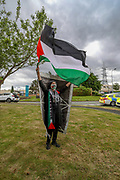 Liverpool, United Kingdom, June 10, 2021: A pro-Palestinian protestor waves Palestinian flag, a banner and shouts pro-Palestine slogans in support of Palestine Action activists group outside an aerospace factory in Runcorn on Thursday, June 10, 2021. Cheshire police continue to maintain their security cordon around the factory after Palestine Action activists scaled the roof and daubed the building in red paint on Thursday, June 10, 2021. They claim the factory produces landing gear for Elbit drones which have been used in the conflict between Israel and Hamas in Gaza. APPH's website says it manufactures hydraulic equipment for military helicopters and fighter jets. (Photo by Vudi Xhymshiti)