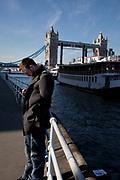 Man listening to his iPod near to Tower Bridge, London.