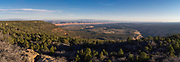 Panoramic image of sunset falling over  Little Baullie Mesa (left), Comb Ridge (receding into the distance), Texas Flat (middle of the image) and the North Fork of Mule Canyon (right), taken from the Manti-La Sal National Forest near Blanding, Utah.
