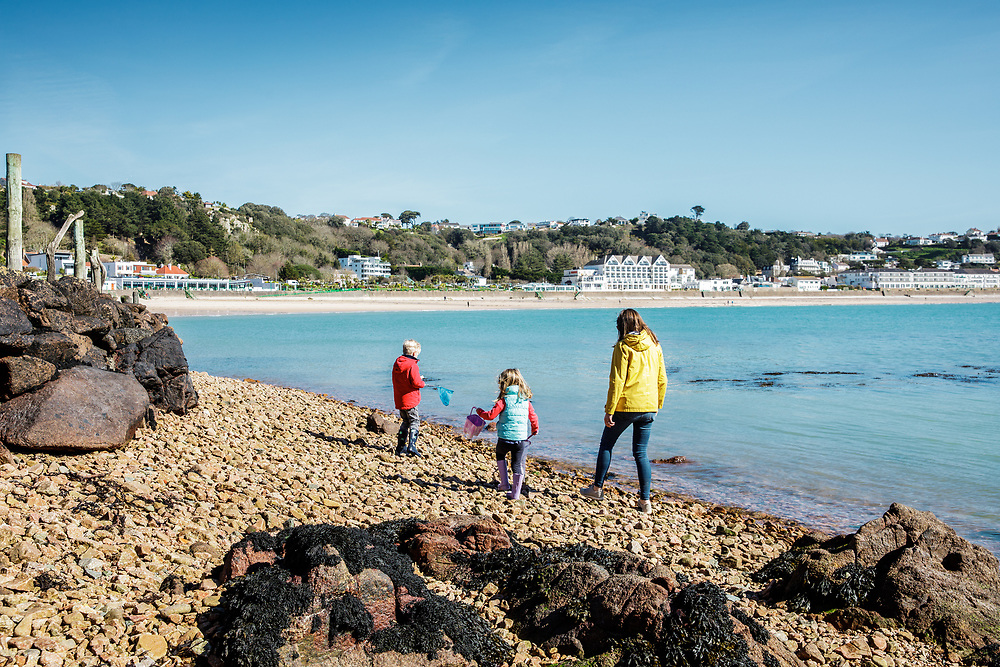 Mum and children exploring the beach at St Brelade's Bay, a popular beach with tourists for its hotels, restaurants, white sand and calm seas in Jersey