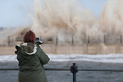 © Licensed to London News Pictures. 03/01/2014.New Brighton, UK . A woman photographs the storm surge as high tide arrives at New Brighton Promenade. Photo credit : Andrew Dawson/LNP