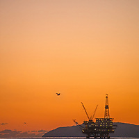 Oil drilling and pumping platforms rise out of the Pacific Ocean near Los Angeles, California. Behind is Santa Catalina Island.