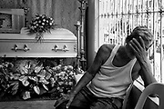 Man mourns the death of his wife in Navotas cemetery before burial in one of the drawers of cement.