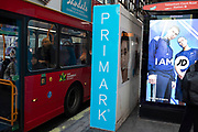 Bus passing a Primark sign on 21st January 2020 in London, England, United Kingdom. Retail is big business on this, the premier shopping street in the UK. Primark sells clothes at the budget end of the market. The company sources cheaply, using simple designs and fabrics in the most popular sizes and buys stock in bulk.