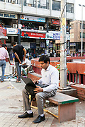 A man works on his laptop at the market in Nehru Place. Nehru Place is a commercial hub in South Delhi that is dominated by electrical and computer and technology shops and New Delhi, India