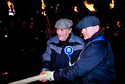 The Biggar Hogmanay bonfire lit at 9.30pm on Hogmanay by local resident John Michie (L) assisted by one of the Biggar Cornets.<br /> <br /> This is probably the biggest new year bonfire anywhere in the UK and continues a tradition going back hundreds of years.<br /> <br /> <br /> (c) Andrew Wilson   Edinburgh Elite media