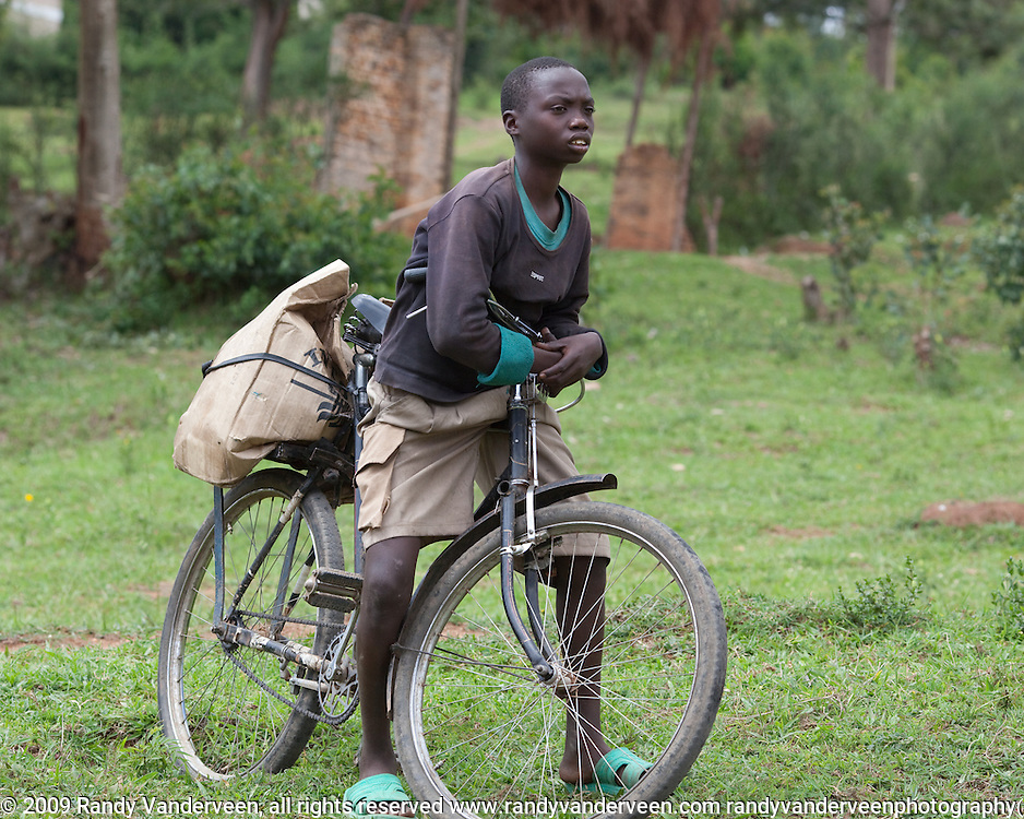 Photo Randy Vanderveen.Nyrusange, Rwanda.A boy on a bike stops and takes a break to watch an ongoing construction project at a school in Rwanda.