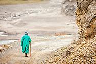 An old Tajik man in a green coat walks on a road away from the viewer in western Tajikistan