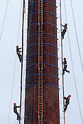 Young apprentices climb ladders to the top of a tall chimney during a steeplejack course in Kings Lynn, Norfolk. Climbing together, the youths haul themselves up a series of ladders to reach the top. Sponsored training is offered through the Steeplejack Industry Training Group Association and CITB-ConstructionSkills for young people aged 16. Applicants for this scheme will have to pass aptitude tests, literary and Maths assessments, and problem solving. Each year, the Steeplejack Industry Training Group and CITB-ConstructionSkills offer 12 places on training courses for trainee steeplejacks and 12 places for trainee Lightning Conductor Engineers.