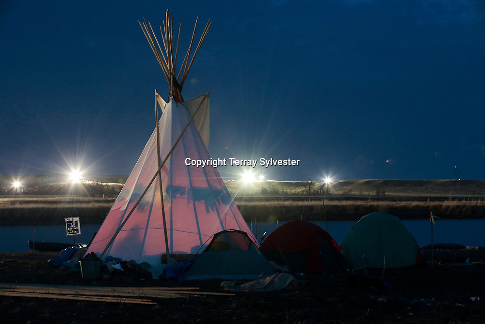 Police floodlights on the Dakota Access oil pipeline route illuminate a ridge above the opposition camp against the pipeline on the banks of the Cannonball River on November 16, 2016. Cannon Ball, North Dakota, United States.