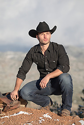 All American cowboy outdoors with a saddle cowboy squatting down on a mountain range