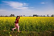 Young school girl, Jasbir Kaur, runs along a yellow mustard field in Chita Kalaan village, Punjab, India.