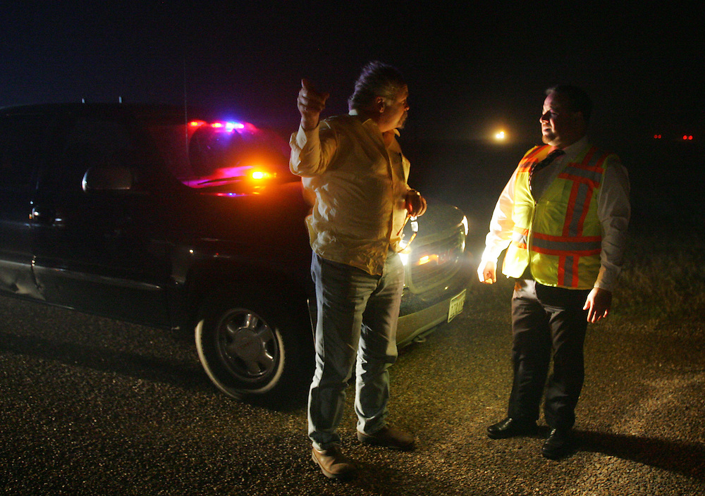 San Manuel, TX - 18 Mar 2008 -.Pilar Rodriguez (right), Assistant City Manager of McAllen, advises local resident Tillmin Welch (left) to prepare to evacuate his home near San Manuel is flames bear down on US 281 Tuesday evening..Photo by Alex Jones / ajones@themonitor.com