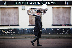 DATE CORRECTION. IMAGES SHOT 14/01/2017 © Licensed to London News Pictures. 14/01/2017. Whittlesey UK. Picture shows a musician arriving in the town of Whittlesey at the 38th Straw Bear festival. In Whittlesey it was the custom on the Tuesday following Plough Monday to dress one of the confraternity of the plough in straw and call him a Straw Bear. The bear was then taken around town to entertain the folk who on the previous day had subscribed to the rustics, a spread of beer, tobacco & beef. The bear was made to dance in front of houses & gifts of money, beer & food was expected. Photo credit: Andrew McCaren/LNP