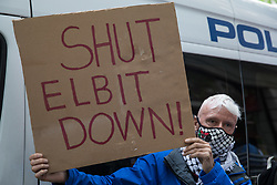 London, UK. 28th May, 2021. An activist from Palestine Action holds up a sign reading 'Shut Elbit Down!' during a protest outside the UK headquarters of Elbit Systems, an Israel-based company developing technologies used for military applications including drones, precision guidance, surveillance and intruder-detection systems. Palestine Action activists were protesting against Elbit's presence in the UK and against British arms sales to and support for Israel.
