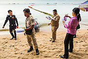 "26 SEPTEMBER 2014 - PATTAYA, CHONBURI, THAILAND:  Pattaya city officials and police walk Pattaya Beach checking on unlicensed businesses on the beach. Pataya, a beach resort about two hours from Bangkok, has wrestled with a reputation of having a high crime rate and being a haven for sex tourism. After the coup in May, the military government cracked down on other Thai beach resorts, notably Phuket and Hua Hin, putting military officers in charge of law enforcement and cleaning up unlicensed businesses that encroached on beaches. Pattaya city officials have launched their own crackdown and clean up in order to prevent a military crackdown. City officials have vowed to remake Pattaya as a ""family friendly"" destination. City police and tourist police now patrol ""Walking Street,"" Pattaya's notorious red light district, and officials are cracking down on unlicensed businesses on the beach.    PHOTO BY JACK KURTZ"