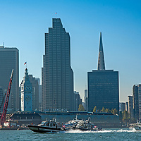 Police speedboats on San Francisco Bay race past downtown skyscrapers.