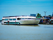 02 AUGUST 2018 - PAK KRET, NONTHABURI, THAILAND: A tourist cruise boat goes up the Chao Phraya River at Ko Kret (also spelled Koh Kret) is a small island in the Chao Phraya River in Nonthaburi province north of Bangkok. It is about 2 km long and 1 km wide. It has seven main villages, the largest and most populous being Ban Mon. Ko Kret was created in 1722 when a canal was dug in the Chao Phraya River to bypass a bend. Most of the people on the island are ethnically Mon, from the hills of western Thailand and eastern Myanmar (Burma). The island is popular as a weekend daytrip from Bangkok. The island is famous for the Mon style pottery made on the island.      PHOTO BY JACK KURTZ