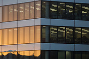 Warm evening sunlight reflected in the windows of generic corporate offices overlooking the river Thames in the heart of the Square Mile, the capitals historical and financial centre, on 1st November 2017, in the City of London, England.