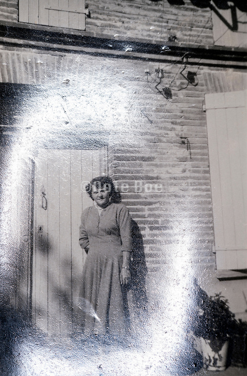 woman posing by door in front of the house with light reflection France 1949
